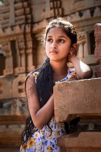 Girl looking away while standing by built structure