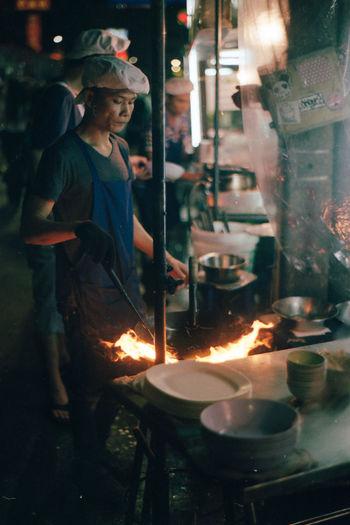 Side view of man preparing food at night
