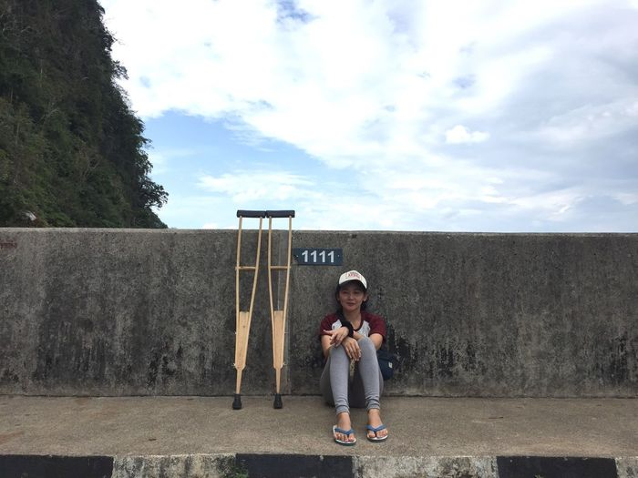 Full length of young woman sitting by crutches against retaining wall on sidewalk
