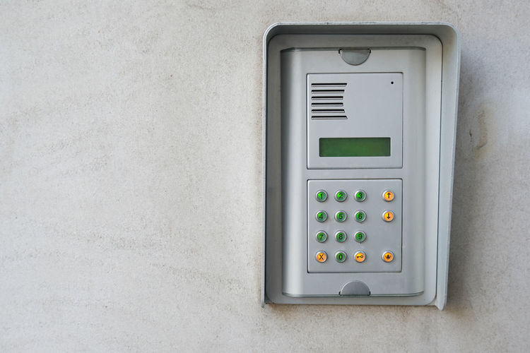Security device intercom on exterior wall of residential building