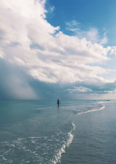Mid Distance View Of Person On Shore At Beach Against Sky