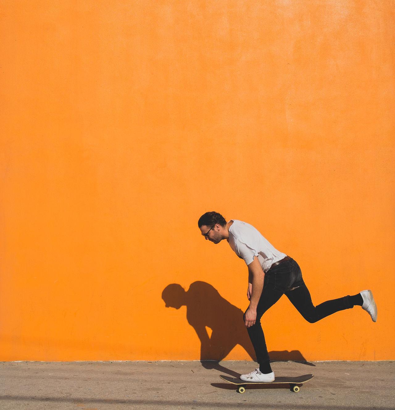 Man skateboarding on street against yellow wall