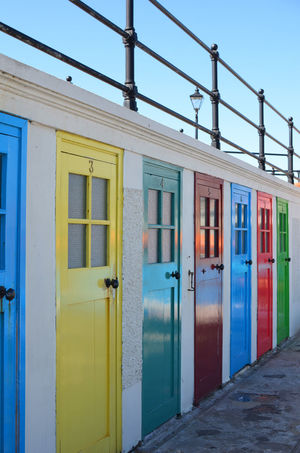 Architecture Beach Beach Hut Beach Huts Blue Building Exterior Built Structure Door Doors Fence In A Row Multi Colored Summer Summertime Vibrant Color Window Paint The Town Yellow