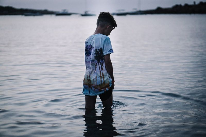 Rear view of boy standing in sea at dusk