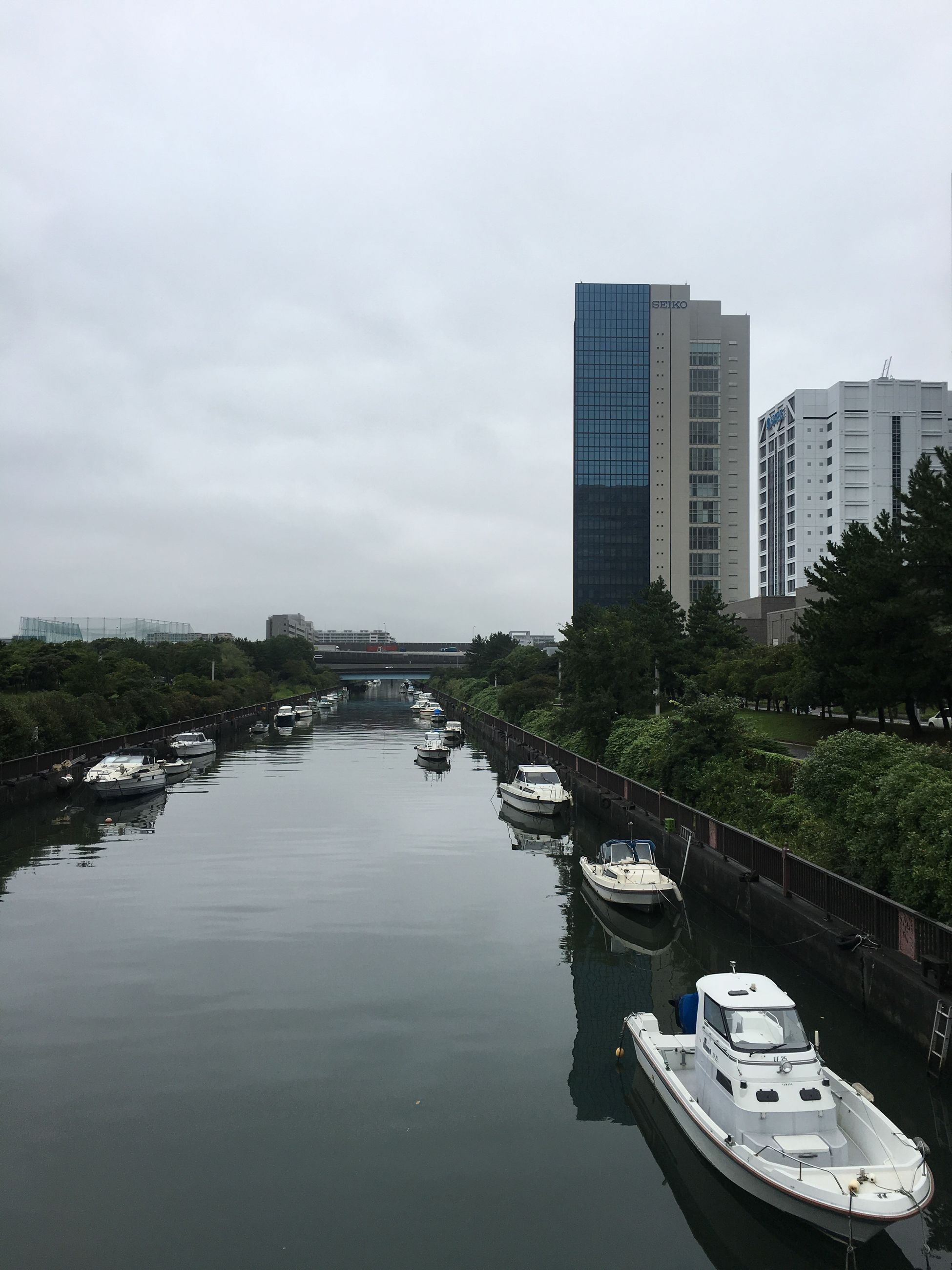 building exterior, architecture, built structure, water, city, transportation, nautical vessel, sky, reflection, mode of transport, waterfront, river, canal, travel destinations, skyscraper, office building, cloud, cloud - sky, modern, city life, day, outdoors, development, building story, no people