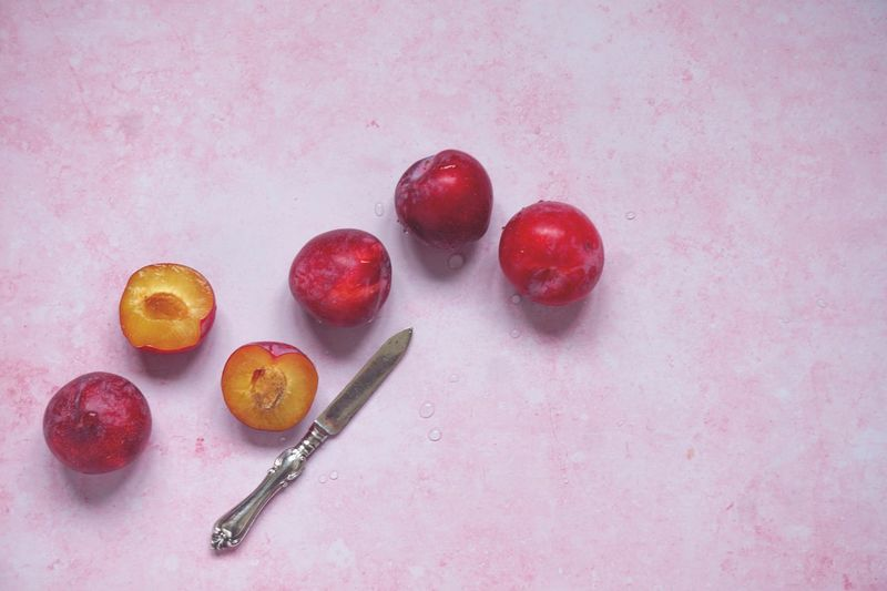 Plums on pink background Healthy Food Healthy Eating Freshness Fruit Plum Food Food And Drink Fruit Freshness Healthy Eating Wellbeing Still Life No People High Angle View Studio Shot Pink Background Directly Above Group Of Objects Table Red Indoors  Ripe Close-up Sweet