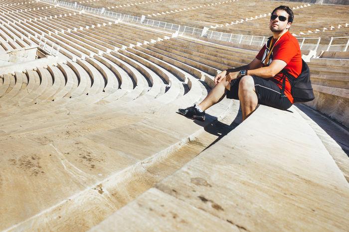 Panathenaic Stadium Athens Casual Clothing Kallimarmaro Leisure Activity Lifestyles Man Marble Olympic Stadium Outdoors Panathenaic Stadium Seat Stadium Sunny Day Tourism Tourist Travel Destinations Vacations Young Adult