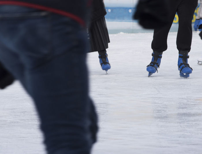 Low section of people ice skating