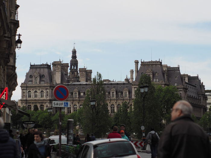 People on road by buildings in city against sky