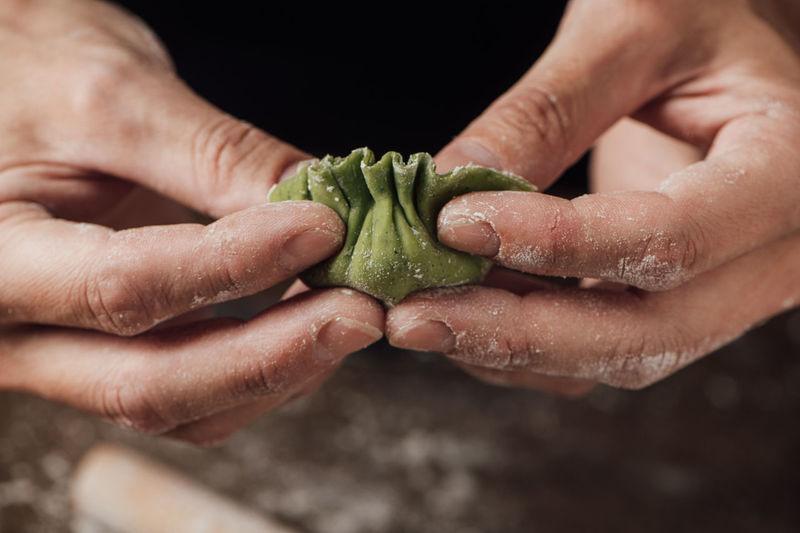 Cropped hands making dumplings