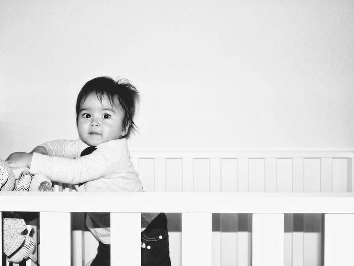 Portrait Of Cute Baby Boy In Crib At Home