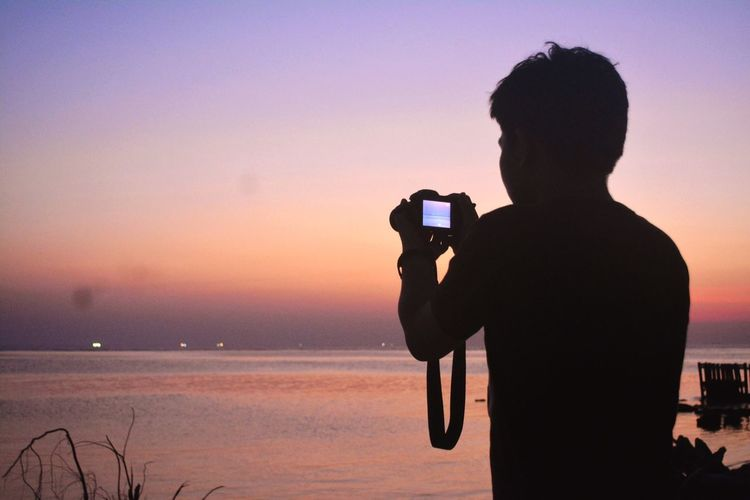 Silhouette man photographing against sea during sunset