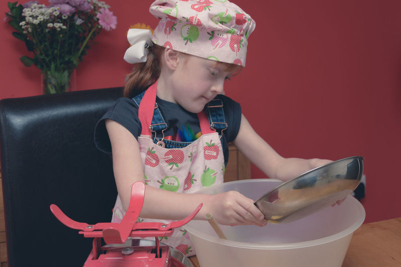 Girl wearing apron mixing flour in container on table at home