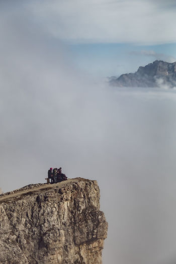View of cliff on mountain against cloudy sky