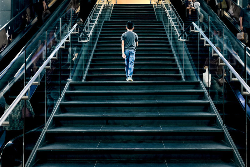 Urban Life Staircase Architecture Steps And Staircases Rear View One Person Moving Up Lifestyles The Way Forward Direction Odd One Out City City Life Motion Escalators Railing Indoor Walking Contrast Odd One Not Normal Non Mainstream