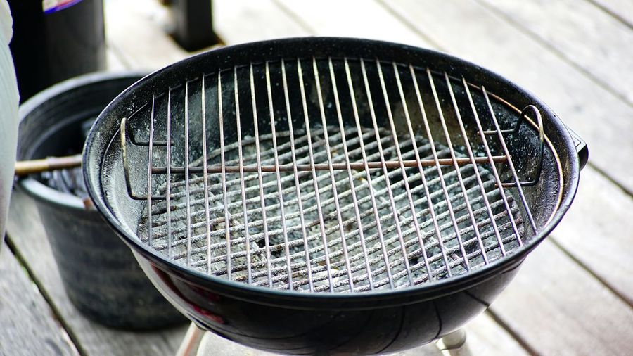 Close-Up View Of Metallic Barbecue Grill On Floorboard