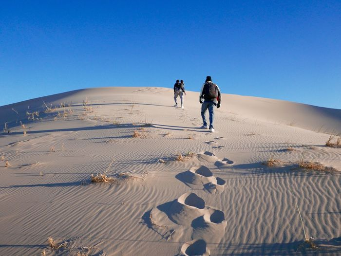 People on sandy desert against clear blue sky