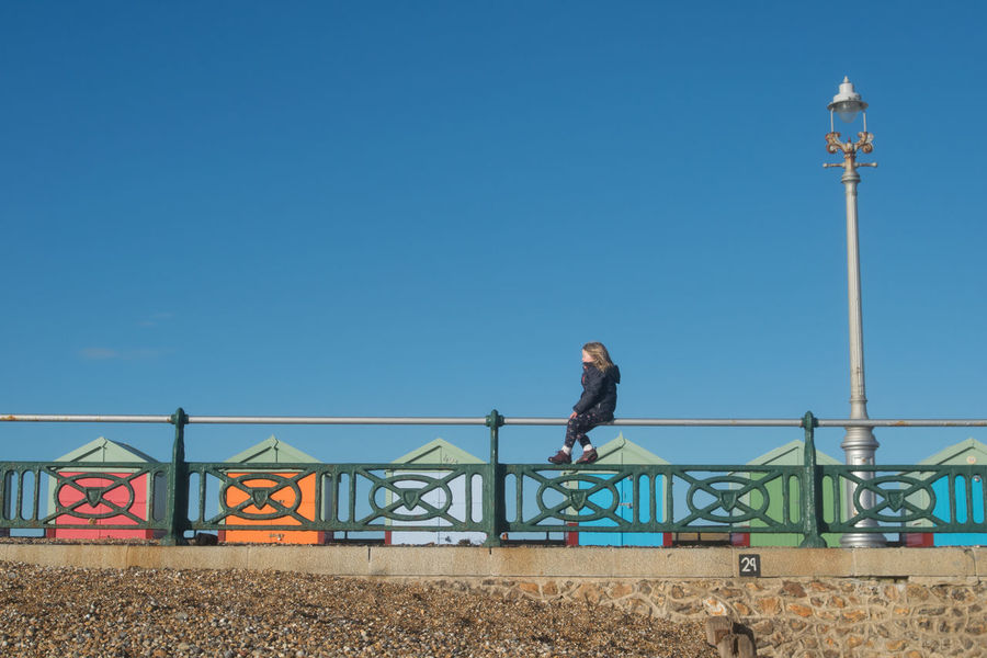 Girl sitting on rail at the beach Colourful Pebble Beach Sitting On The Fence Wall Beach Beach Front Beach Huts Blue Blue And Brown Blue Sky Clear Sky Day Fence Girl Lampost Leisure Activity One Person Outdoors Pebbles People person Real People Sitting On Fence Sky Young Girl