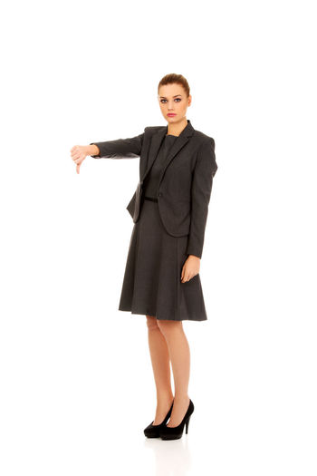 Portrait of businesswoman gesturing thumbs down sign against white background