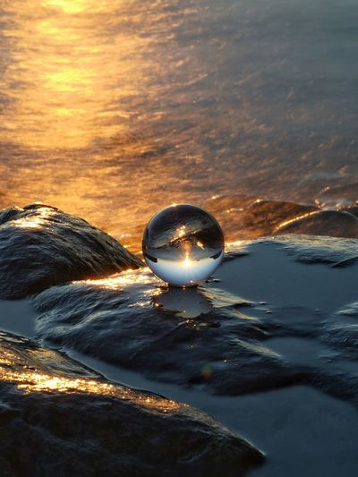 Close-up of crystal ball in sea against sunset sky