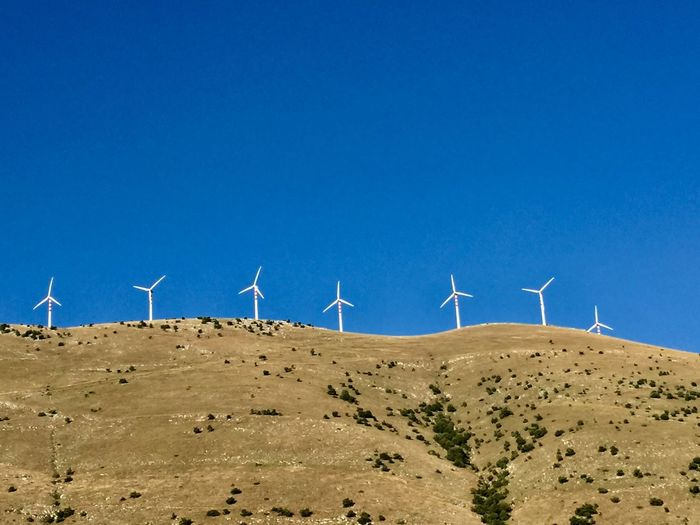 Wind turbines on mountain against clear blue sky