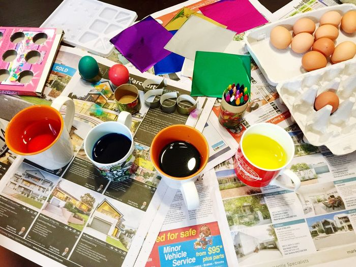 High Angle View Of Easter Eggs With Craft Products On Table