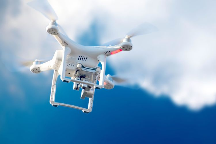Low angle view of drone flying against blue sky