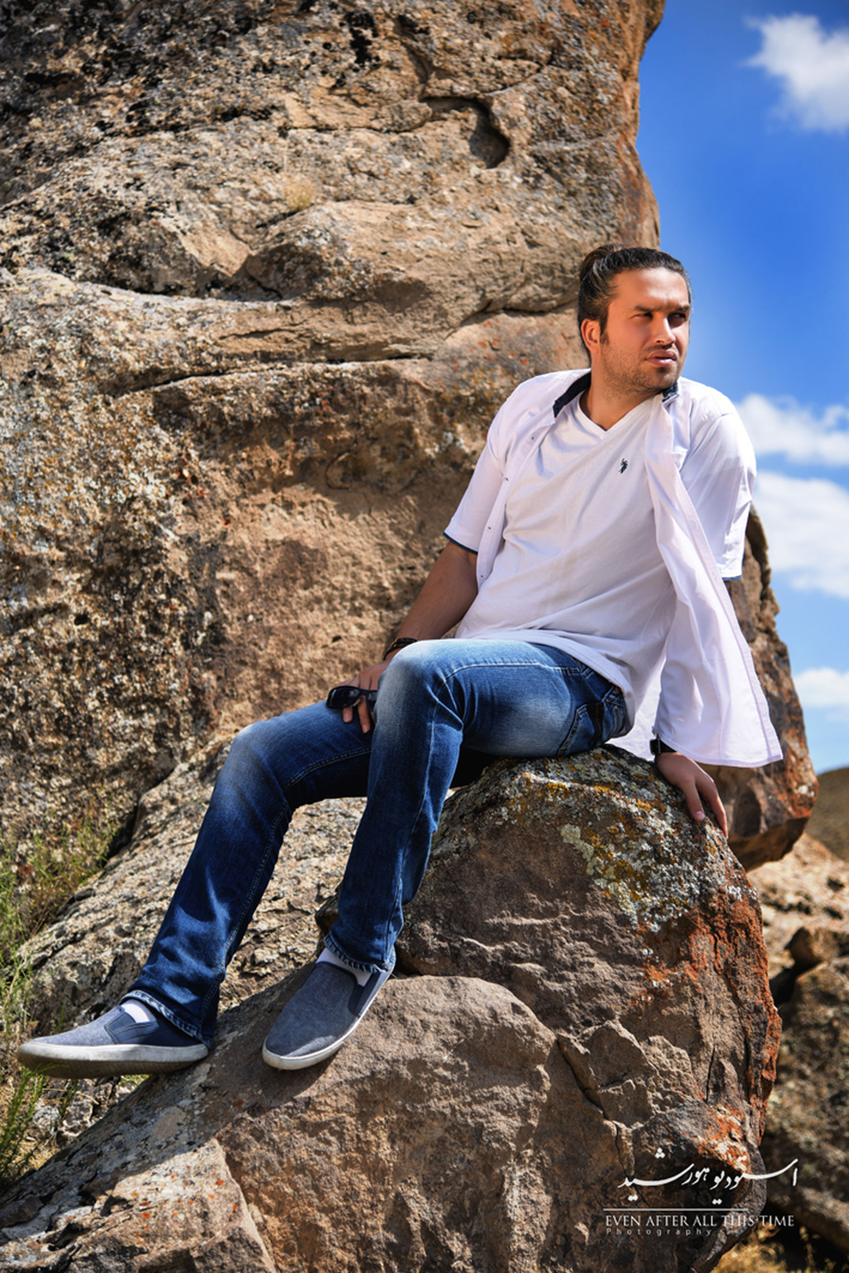 rock - object, sitting, full length, person, casual clothing, young adult, leisure activity, rock formation, lifestyles, cliff, mountain, rock, getting away from it all, geology, mature adult, relaxation, tourism, outdoors, non-urban scene, tranquility, rocky, sky