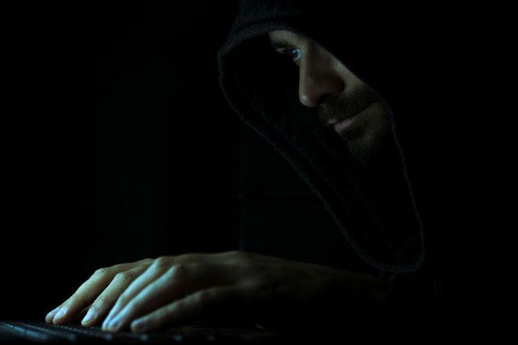 Computer hacker tying on keyboard against black background