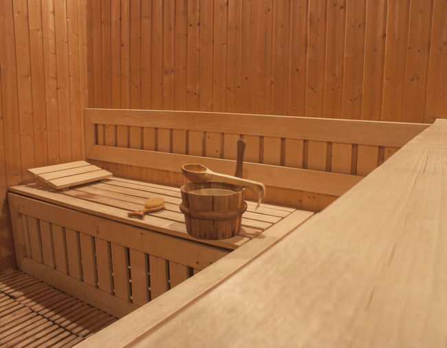 Empty bench with wooden bucket and spoon against wall