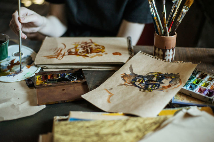 Art And Craft Selective Focus Craft Indoors  Creativity Table One Person Paintbrush Brush Human Hand Real People Occupation Paper Hand Publication Human Body Part Art And Craft Equipment