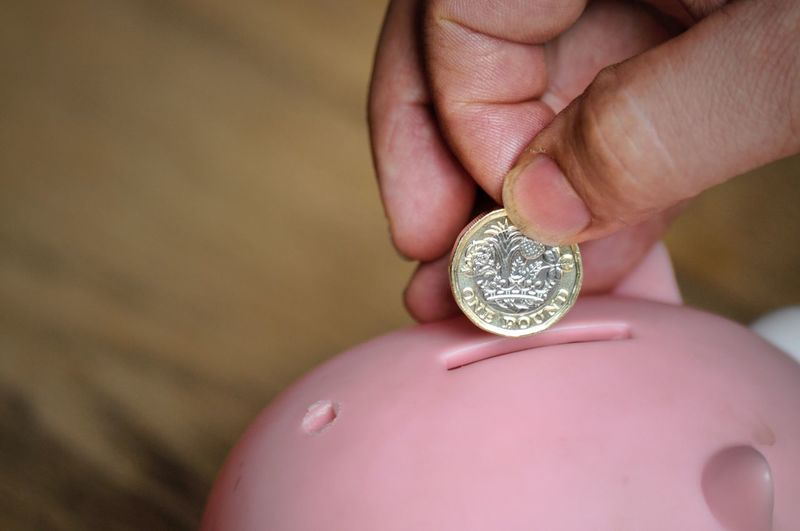 Close-Up Of Hand Holding Coin Over Piggy Bank