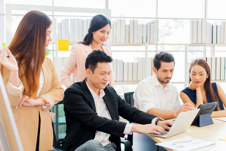 Group of people using phone while sitting in office