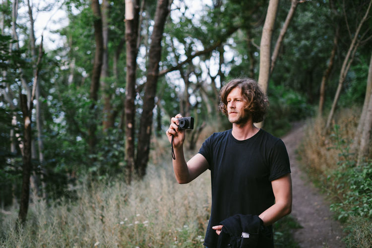 Young man photographing in forest