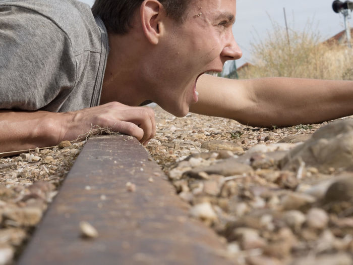 Close-Up Of Man Shouting While Lying On Railroad Track