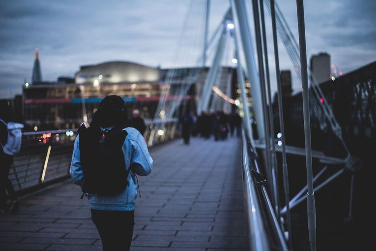 Rear view of woman walking on suspension bridge in city