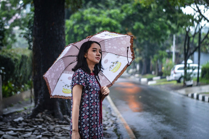 Young woman holding umbrella while standing on roadside