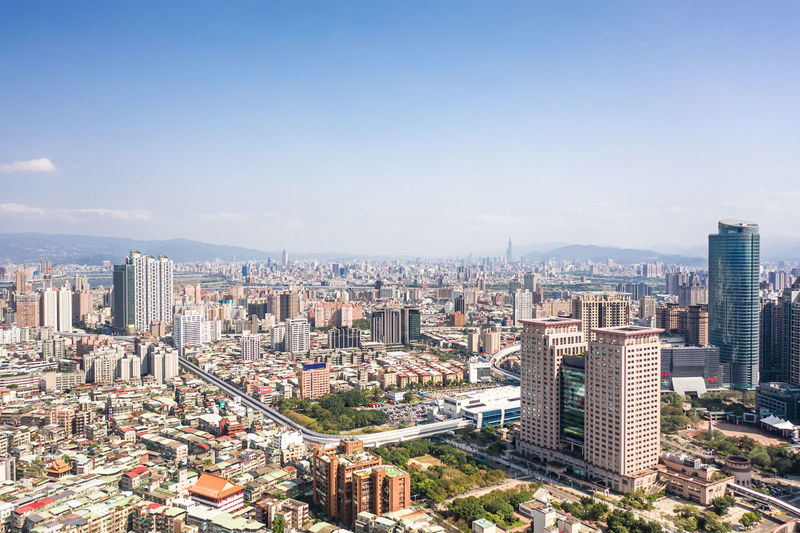 Aerial view of cityscape against blue sky