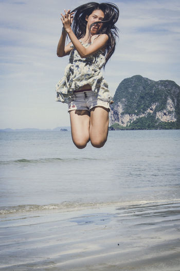 Young woman jumping at beach against sky