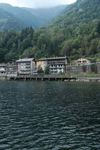 Scenic view of river by buildings against mountain