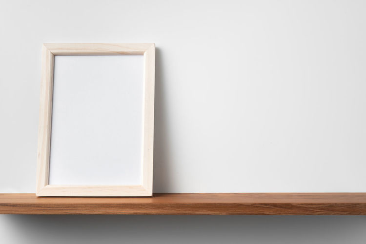 Close-up of empty table against wall at home