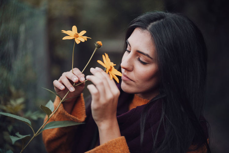 Close-up of young woman smelling flower at forest