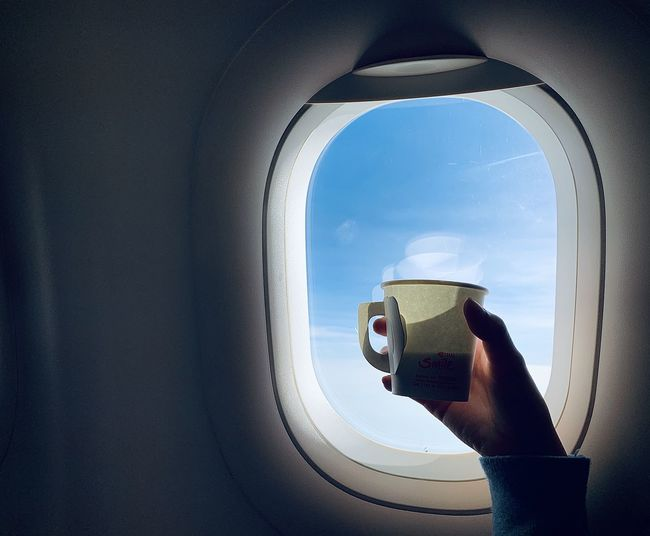 Close-up of person holding coffee by airplane window