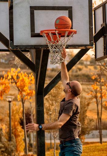 Man standing by basketball hoop
