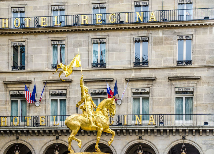 "Paris, Francw - March 17, 2012: The golden statue of Saint Joan of Arc on the Rue de Rivoli in Paris, Photographers shooting the profile of the statue with the hotel ""Regina"" in the background Architecture Art Balcony Building Exterior City Day Equestrian Ermornin Façade France Gold HERO History Horse Joan Of Arc King - Royal Person No People Outdoors Paris Royal Person Royalty Sculpture Statue Window Worrior"