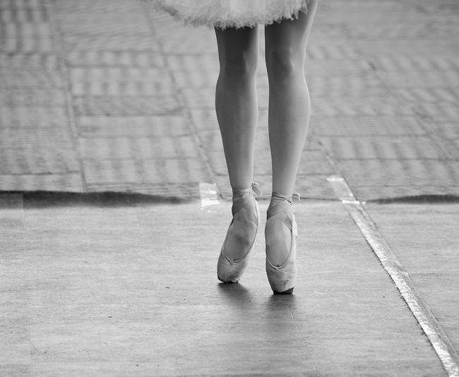 Low section of ballerina dancing on floor