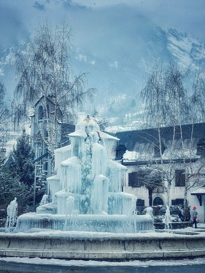 Fountain by building during winter