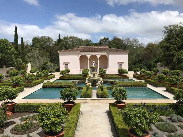 Fountain in garden against sky
