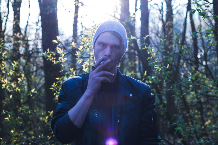Portrait of man smoking cigarette in forest