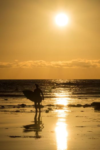 Coming in after a surf session at Swami's Beach in Encinitas, California San Diego Encinitas Surfer Water Sky Sea Sunset Silhouette Land Go Higher Reflection Horizon Over Water Beauty In Nature Beach Sun Scenics - Nature Real People Horizon Orange Color Lifestyles Nature Outdoors One Person Sunlight